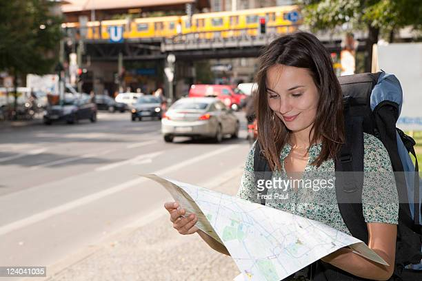 Young backpacker looking at a city map