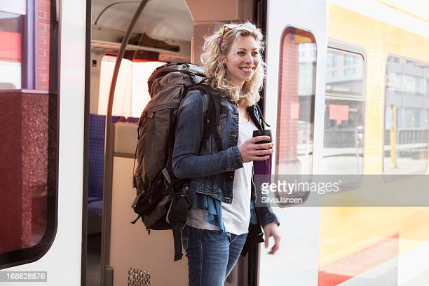 young backpacker woman arriving with train
