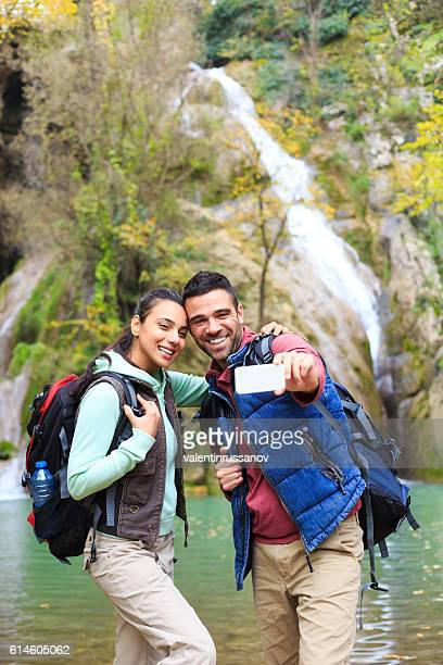 Young backpackers making selfie in front of waterfall