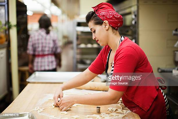 Young baker preparing food in kitchen