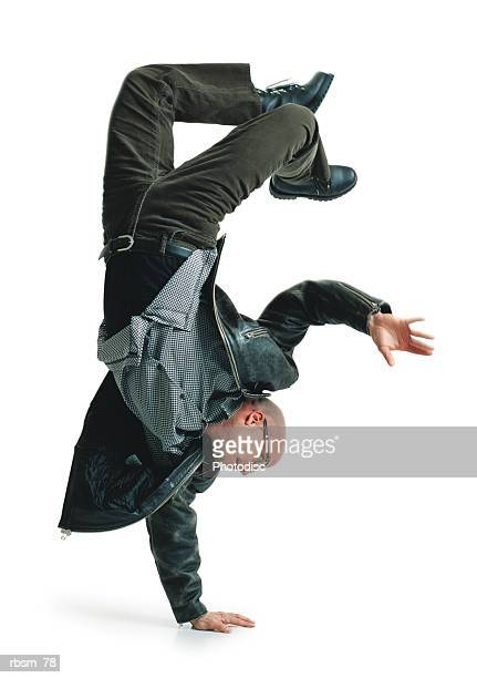 young bald male modern dancer in green pants and leather jacket balances upside down on one hand