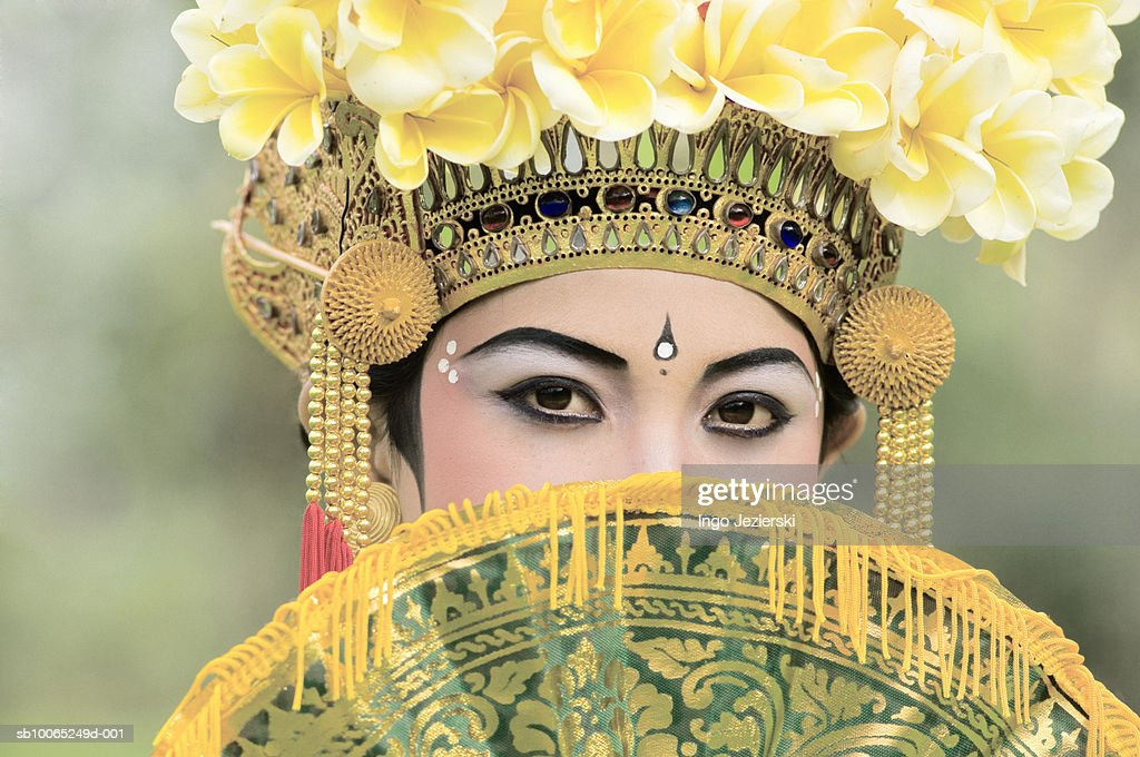 Young Balinese girl (13-14) dancer behind fan, portrait : Stock Photo