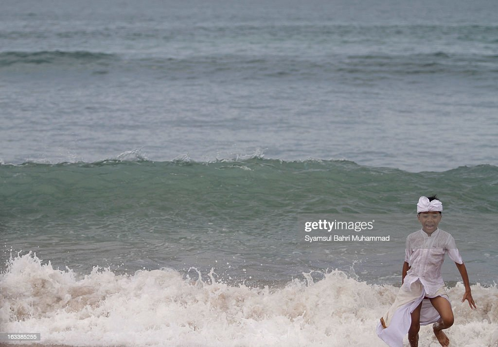 A young Balinese Hindu devotee gestures as he plays on the seashore during Melasti Ritual ceremony on March 9, 2013 in Denpasar, Bali, Indonesia. The Melasti Ritual is held annually ahead of the Nyepi Day of Silence a ceremony intended to cleanse and purify the souls of the Balinese Hindu participants. Nyepi is a Hindu celebration observed every new year according to the Balinese calendar. The national holiday is one of elf-reflection and meditation and activities such as working, watching television or travelling are restricted between the hours of 6am and 6pm.