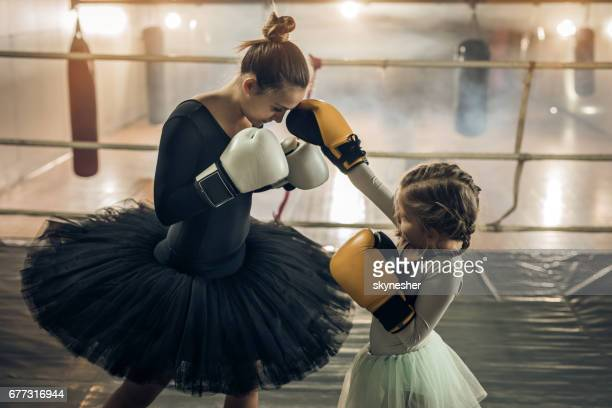 Young ballerina and small girl exercising boxing in the ring.