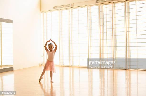 Young ballerina dancing in a dance studio.