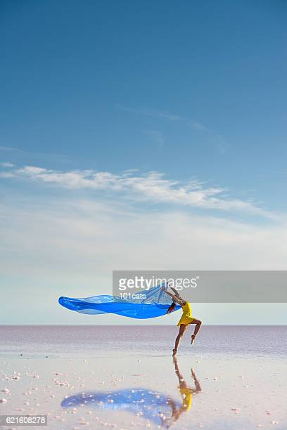 Young ballerina dancing on the salt lake with color tulle