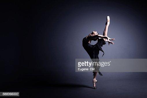 Young ballerina in a black suit is dancing in dark : Stock Photo