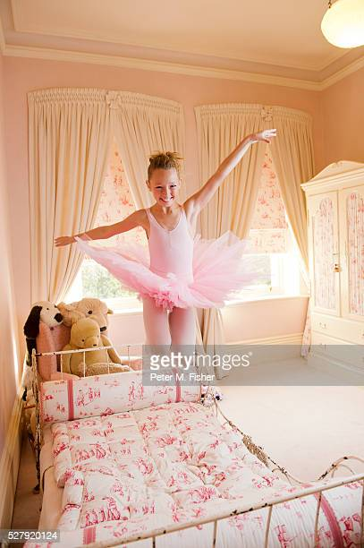 Young ballerina jumping on bed