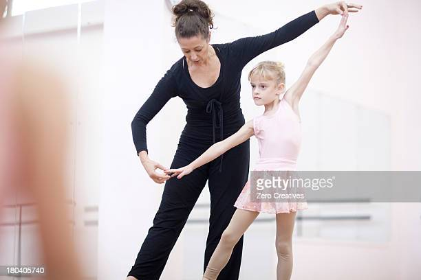 Young ballerina practicing pose with teacher