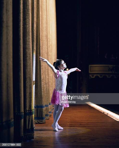 Young ballerina (6-8) standing on stage with arms outstretched