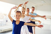 Young little cheerful girls performing ballet and smiling looking at camera in the class.