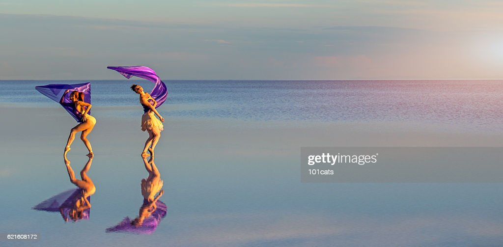 Young ballerinas dancing on the salt lake with color tulle : Stock-Foto