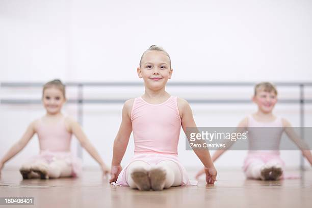 Young ballerinas in pose whilst sitting on floor