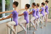 Young ballerinas training at ballet barre. Group of ballet dancers posing near ballet barre in ballet studio. Difference between gymnastics and ballet.