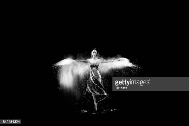 Young ballet dancer jumping into white powder cloud