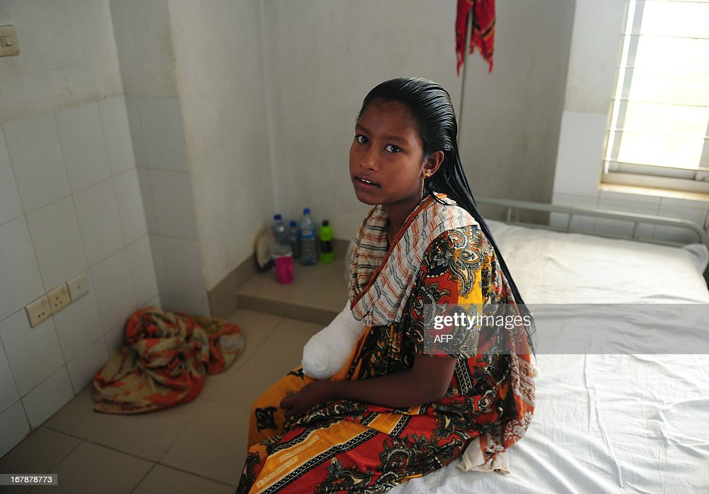 A young Bangladeshi garment worker who was rescued from a building that collapsed sits in a hospital bed with an amputated arm, in Savar, on the outskirts of Dhaka, on May 2, 2013. Bangladesh authorities have suspended the mayor of Savar satellite town outside the capital for approving the faulty construction of a building that collapsed last week, killing 429 people. AFP PHOTO/ Munir uz ZAMAN