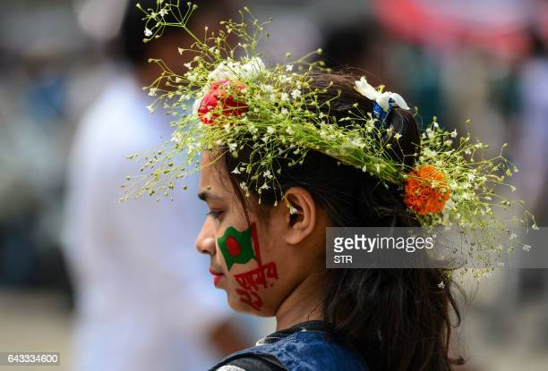 A young Bangladeshi woman wears the national flag painted on her face as she participates in a rally near the monument for Bangladesh's Language...