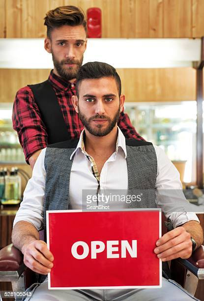 Young Barbers Showing an Open Sign