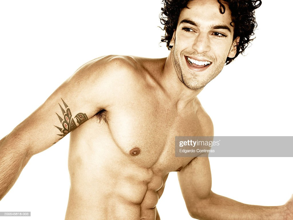 Young bare-chested man, looking away, smiling : Stock Photo