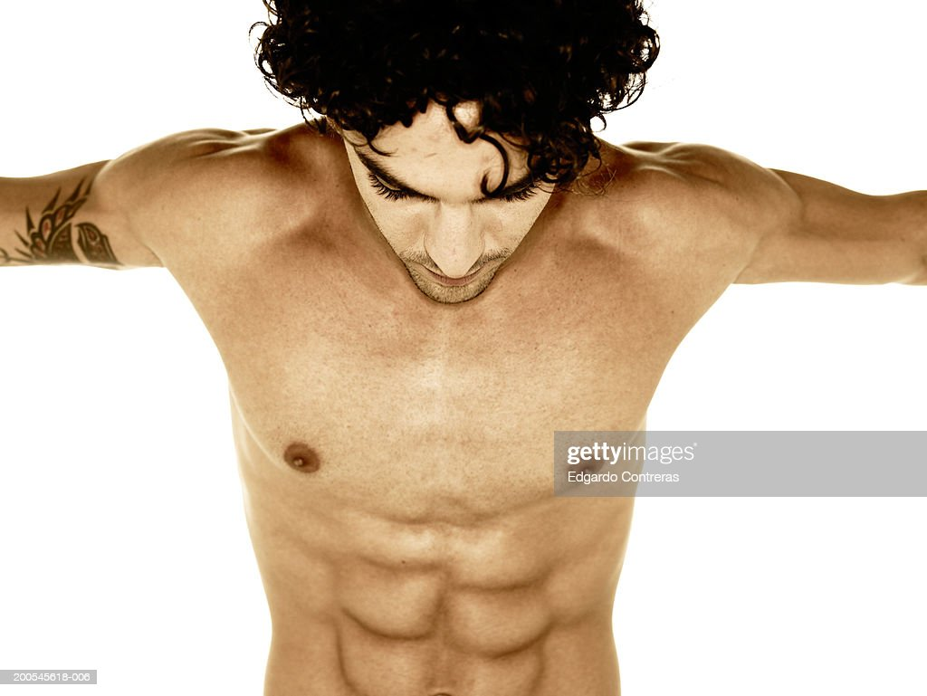 Young bare-chested man with arms outstretched, looking down, upper half : Stock Photo