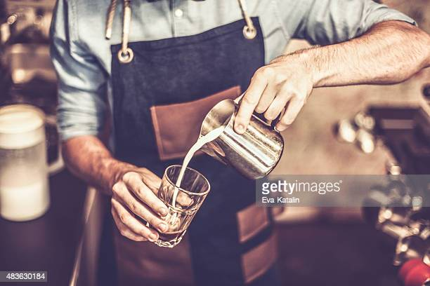 Young barista is making a coffee