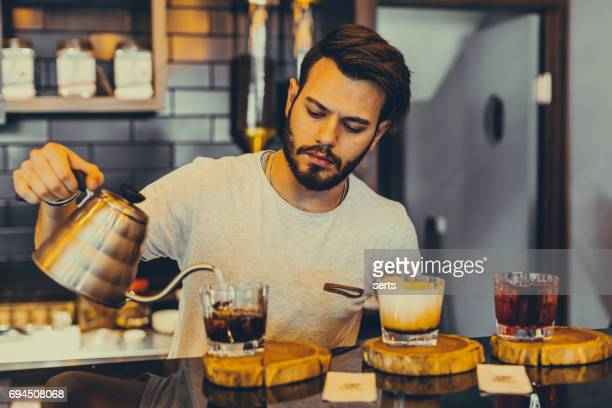 Young barista is making a cold coffee in cafe shop