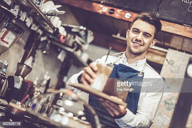 Young barista is offering a coffee speciality