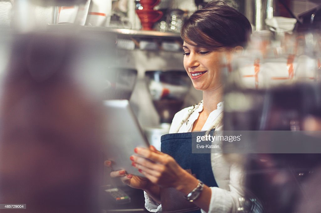 Young barista is using a digital tablet : Stock Photo