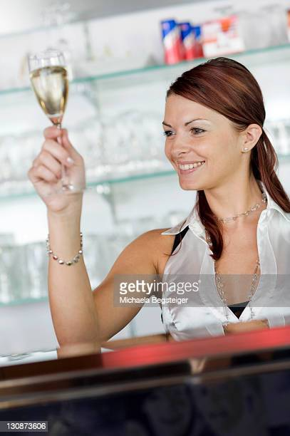 Young barmaid with champagne glass behind the bar