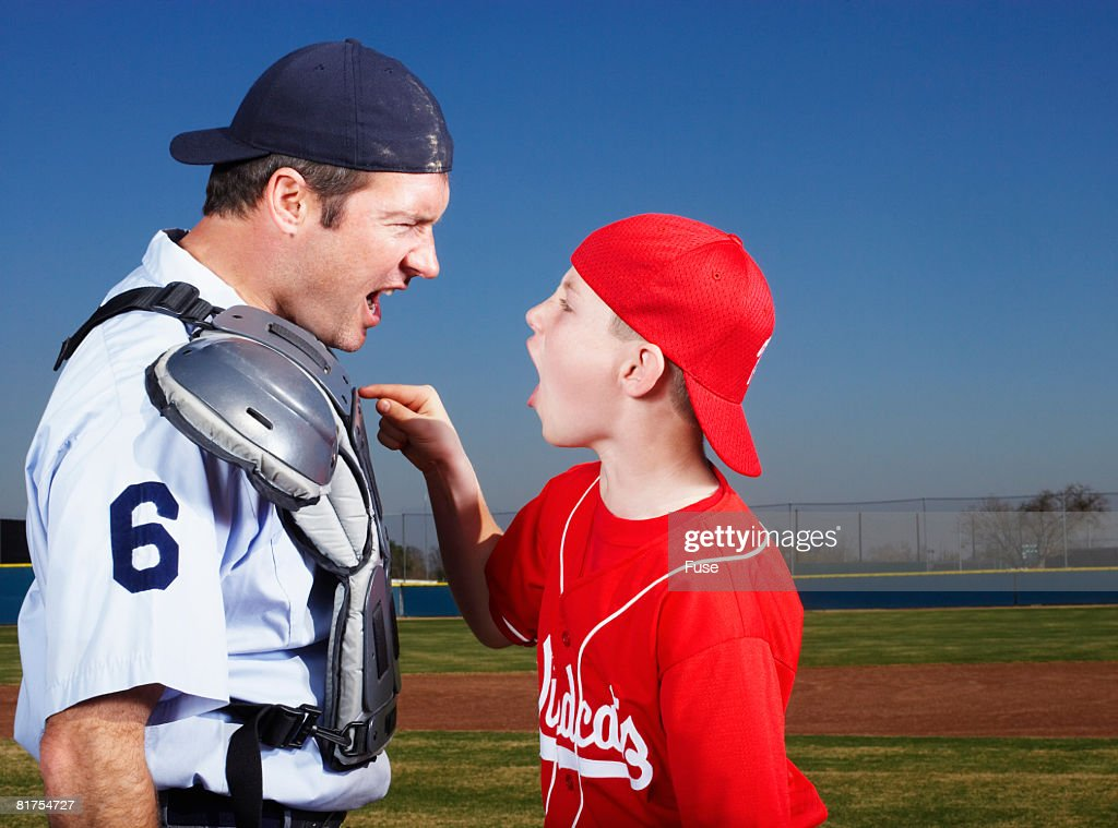 Young Baseball Player Arguing with Umpire