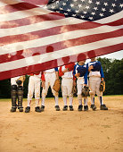 Young baseball players partially hidden by American flag