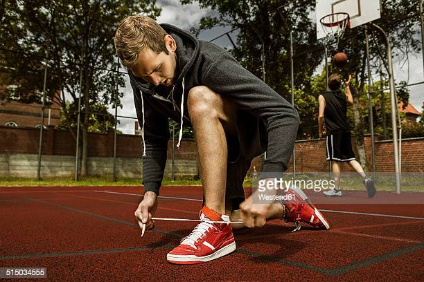 Young basketball player doing up the shoelaces