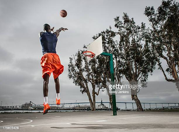 Young basketball player jumping to score