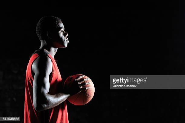 Jeune Joueur de basket-ball avec une balle-vue de côté