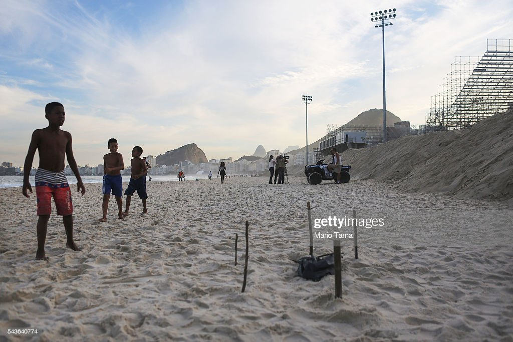 Young beachgoers walk near a body part, covered in a plastic bag, which was discovered on Copacabana Beach near the Olympic beach volleyball venue (TOP R) on June 29, 2016 in Rio de Janeiro, Brazil. Parts of a mutilated body were discovered on the sands of the beach while it remains unknown how the person died. The Rio 2016 Olympic Games begin August 5 amidst an economic crisis in the country.