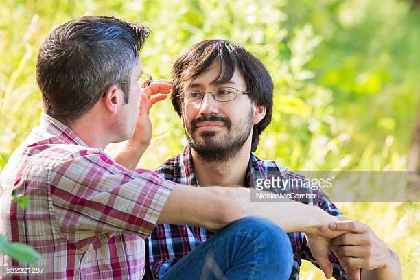 Young bearded gay Hispanic man enjoying park romance with boyfriend