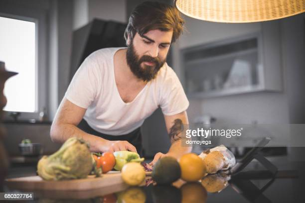 Young bearded man cutting vegetable in the kitchen and reading recipe on digital tablet