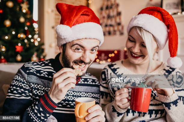 Young bearded man eating cookie, enjoying holidays and Chirstmas