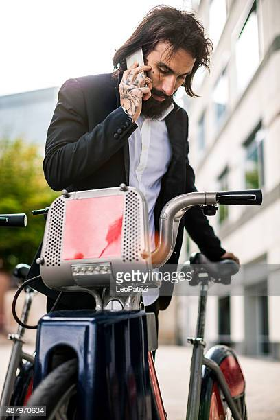 Young bearded man in business taking city bike in London
