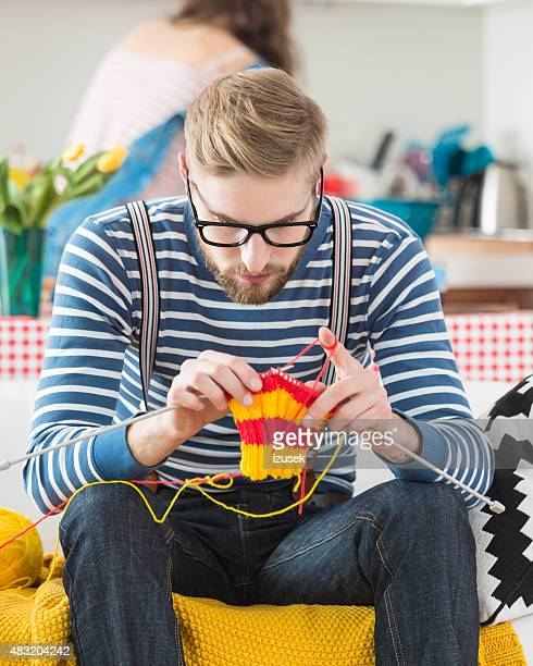 Young bearded man knitting