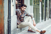 Young bearded man, model of fashion, sitting in an urban step wearing casual clothes. Guy with beard and modern hairstyle looking away in the street.