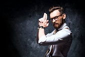 Young stylish bearded man in glasses posing with a finger gun.