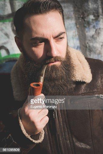 Young bearded man smoking pipe by graffiti wall