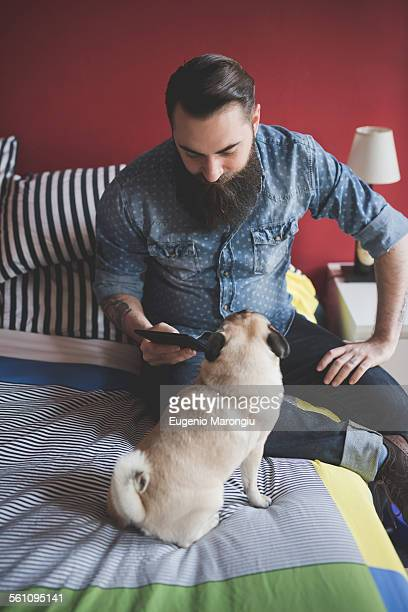 Young bearded man using smartphone on bed