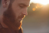 young bearded man with closed eyes on the background of the sun's rays