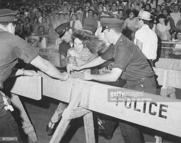 A young Beatles' fan tries to break through a police line at Shea Stadium concert