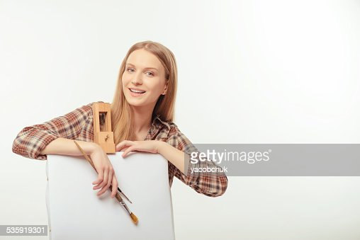 Young beautiful artist posing with a drawing easel : Stock Photo