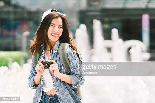 Young beautiful Asian backpack traveler woman using digital compact camera and smile, looking at copy space. Journey trip lifestyle, world travel explorer or Asia summer tourism concept : Foto stock