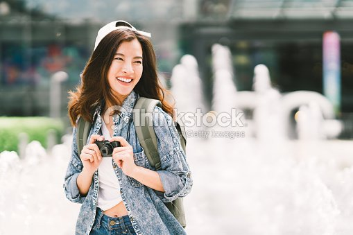 Young beautiful Asian backpack traveler woman using digital compact camera and smile, looking at copy space. Journey trip lifestyle, world travel explorer or Asia summer tourism concept : Stock Photo