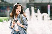 Young beautiful Asian backpack traveler woman using digital compact camera and smile, looking at copy space. Journey trip lifestyle, world travel explorer or Asia summer tourism concept